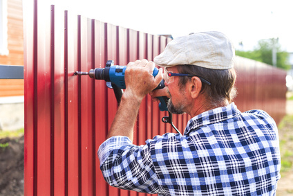 Expert fence installer drilling aluminum fence panels to hold in place