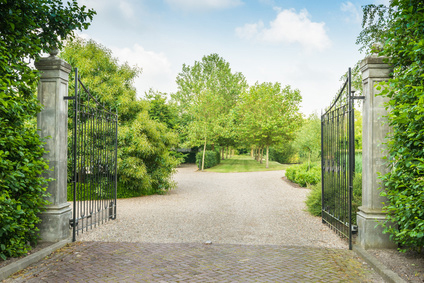 Wrought iron gate opening to estate home driveway